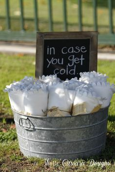 To eliminate the need for heat lamps, the bride bought inexpensive blankets to share with the guests at her outdoor wedding.