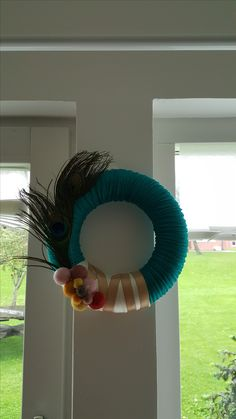 Wreath with mint ribbon,beige and sandgold satin decorative band ribbon,peacock feathers and nepal felt balls. I used 24cm yarn and hot glue to glue the blue ribbon over the yarn. Then I chose where I wanted to put the decorative ribbons and bands and hot glued them over the blue ribbon and complemented with the peacock feathers and nepal felt balls, to give a different touch.