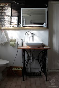 Bathroom vanity created from repurposed sewing machine and vessel sink