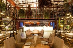 vivarium restaurant ~ hypothesis converts tractor warehouse into plant-filled restaurant in bangkok, Thailand  iron doors, steel pipes, dead branches, and tree roots decorate the interior. the design team thought of a terrarium as a concept. a scaffolding system occupies the interior, forming shelving for the decoration. a lush green-scape of hanging plants populates the upper volume of the double height space.