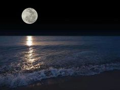 Moon over the rolling ocean tide and waves; walk the sandy beach in the moonlight