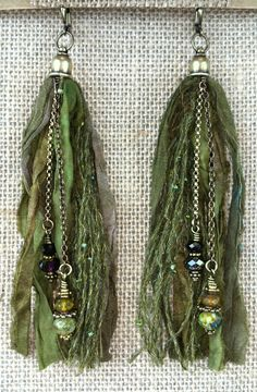 Fun and playful, like Sigmund the Sea Monster, these tassel earrings are a delight in green. Reclaimed, sari silk ribbon and hand selected, sparkling yarn make a beautiful seaweed backdrop of chains t