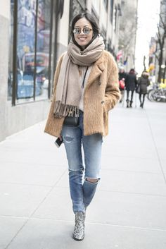 A camel coat paired with a scarf and ripped jeans.