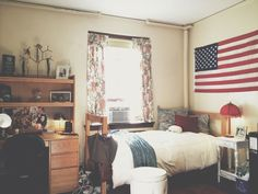 Cozy Dorm Room Looks Like Home - Who said dorm rooms have to look sterile or juvenile? This room could be in anyone's home with the floral curtains, throw pillows, and fringed lamp. Any patriotic home, that is, as evidenced by the U.S. flag over the bed.
