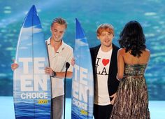 Actors Tom Felton and Rupert Grint accept the Harry Potter awards from actress Zoe Saldana onstage during the 2011 Teen Choice Awards