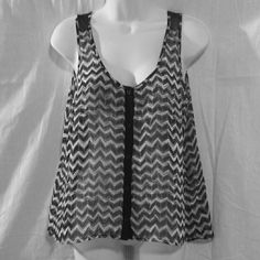 Candies Small Sheer Flowy Tank Top This is a very pretty tank top from Candies that has black and white zig zag designs all over it.  The back has an opening between the designs that has solid black cloth.  This top is sheer and very flowy! This is size small. #sheer #flowy #zigzag #tanktop #small #blackandwhite Candie's Tops Tank Tops