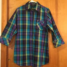 NWOT Foxcroft plaid tunic blouse size 6 Foxcroft blouse is tunic length. Wear as is or belted. Front button closure with buttons covered in plaid material. There is a left side breast pocket, 3/4 length cuffed sleeves and 5 inch side slits. Gorgeous colors of deep purple, greens and blues. There is a replacement button sewn on interior tag. Made from 100% wrinkle free cotton. Underarm to underarm 19 1/2 inches. Shoulder to bottom of blouse 29 inches Foxcroft Tops