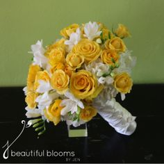 Bridal bouquet of white hydrangea, yellow ranunculus, yellow roses, yellow spray roses, and white freesia by Beautiful Blooms by Jen.