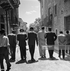Mafia boss Charles 'Lucky' Luciano (centre, 1897-1962) walking with his henchmen, with their backs to the camera, in Sicily, Italy, 31 December 1948. Luciano assists one of the men, who is carrying a stick.
