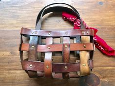 Handmade leather belt basket bag perfect for toting the essentials. This medium sized shoulder bag is a cross between a shoulder bag and a market tote. Leather belts are woven into a unique one-of-a-kind hybrid basket bag. Each bag is named after a mountain here in my home state of New Hampshire . I call this bag the Tecumseh after the 4,003 foot rugged peak in northern New Hampshire. Crafted from leather belts that are riveted together with antique brass colored Chicago screws. Each belt…