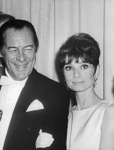 """The actress Audrey Hepburn photographed with the actor Rex Harrison (holding his Oscar, category Best Actor, about his performance in """"My Fair Lady"""") at the Santa Monica Civic Auditorium, in Santa Monica, a beachfront city in western Los Angeles County, California (USA), in the backstage after the ceremony of the 37th Annual Academy Awards, on April 05, 1965.Audrey was wearing:Evening gown: Givenchy (of white satin, sleeveless and with a jewel neckline, the model presents a geometric detail…"""