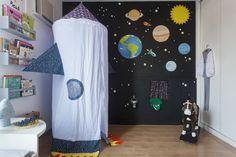 A mãe de Isabela pediu ao ateliê Nina Moraes apenas uma maquiada na brinquedoteca. O resultado é a parede preta, em uma divertida viagem pelos planetas.