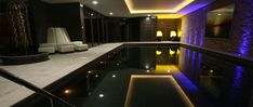 Marvelous Indoor Pools With Black Wall Design And Purple Lighting