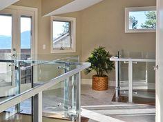 Neutral Hallway With Modern Glass Railing