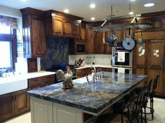 This Shell Beach home features a Blue Bahia island, white engineered stone main countertops, and a Blue Bahia stove backsplash. In this particular scenario, the island granite was unseamed and required a crane to bring it up to the second story!