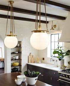 Old World Brass Globe Pendants And Black Kitchen Cabinets With Brass Hardware | Lacanche Range