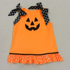 Girls' corduroy jumper with pumpkin face and polka dot ruffle. Pair it with leggings and a long sleeve T for a perfect for October outfit. $32. On sale now at www.facebook.com/jdoriginals