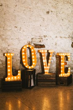 LOVE marquee letters sitting on crates at the reception | Image by Oak & Myrrh Photography