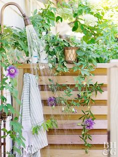 outdoor shower with wood side and purple flowers growing around