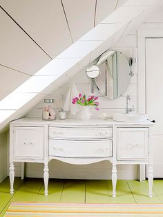Vintage Cottage  Under the Eaves  Space-saving moves and budget-friendly materials add function and style to this small attic bathroom. An old sideboard-turned vanity tucks neatly beneath the eaves. The vanity's surface was gently aged, which blends well with the bathroom's vintage-meets-cottage look.