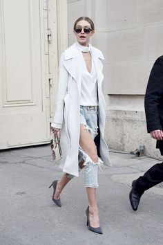 Gigi Hadid wears a plunging-neckline top, long coat, distressed jeans, round sunglasses, and suede pumps