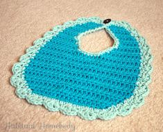 Crochet baby bib with scalloped border.