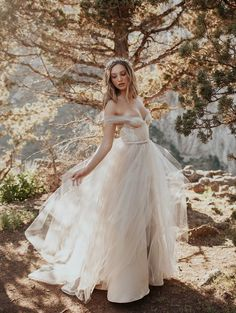 Billows of watercolor tulle in the palest shades of champagne and opal. Shimmering paillettes decorate the bustier bodice, and a jeweled belt encircles the fitted waist. Soft tulle sleeves whisper from your shoulders. All in all, you are a faerie queen.