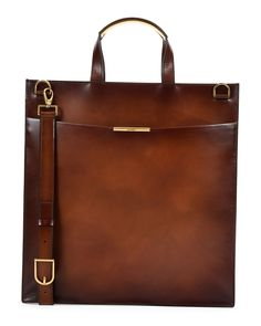 "Salvatore Ferragamo ""Edition"" tall briefcase in leather. Flat tote handles with gold bar detail. Open top. Attached coin pouch. Front slip pocket with gold embossed logo. Made in Italy."