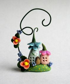 This miniature fairy house with blossom vine is an original design and creation by artist C. Rohal. It is completely hand made from mixed media, hand sculpted from polymer clay and hand painted and it is wonderful. It is adorable. It is filled with tiny details. It has been sealed with polycrylic sealer and comes initialed and dated by the artist. It is truly a tiny treasure :)