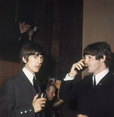 George Harrison, left, and Paul McCartney of the Beatles have refreshments at Australia House, London, 1964. (AP Photo)