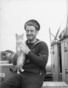 ON BOARD A DESTROYER ON ESCORT DUTY. OCTOBER 1940, ON BOARD THE DESTROYER HMS VANITY. Leading Seaman Lawrence with the ship's cat mascot.