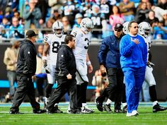 Carson Palmer #3 of the Oakland Raiders is escorted off of the field after being injured against the Carolina Panthers during play at Bank of America Stadium on December 23, 2012 in Charlotte, North Carolina.