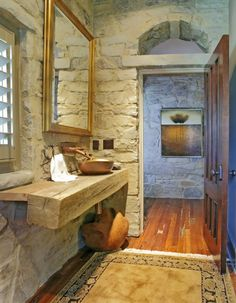 brilliant use of a small hall bath space. Two reclaimed wood square logs joined, with a tiny vessel sink and wall mounted hardware.  I would have used a different colored mirror, but I love the limestone rock walls