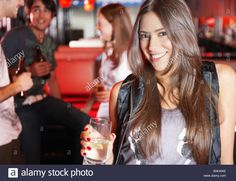 Download this stock image: Woman holding beverage in nightclub smiling - B0KAWE from Alamy's library of millions of high resolution stock photos, illustrations and vectors.
