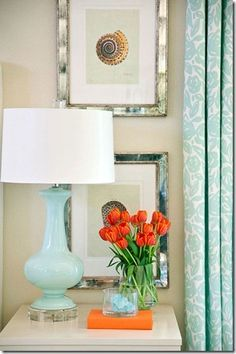 Neutral walls, a sky blue lamp base with a white shade, pretty blue and white curtains, and orange tulips.  Beautifully styled spot!