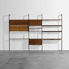 Lot 110: George Nelson & Associates. CSS (Comprehensive Storage System). 1959, walnut, enameled aluminum, aluminum. 129½ w x 20 d x 90 h in. result: $4,763. estimate: $5,000–7,000. This CSS unit is comprised of four uprights, one desk top with three trays, one cabinet with eight drawers, one  cabinet with one flip-top door and two sliding doors concealing storage, two side panels, one drop-down door and eight shelves, two of which have lights. Signed with impressed manufacturer's mark to…