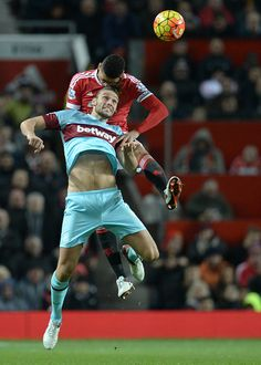Manchester United's English defender Chris Smalling and West Ham United's English striker Andy Carroll jump for a header during the English Premier...