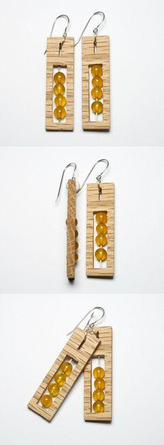 Ręcznie wykonane kolczyki z drewna dębu czerwonego. W środku zostały zamontowane miodowe koraliki z agatu na srebrnym sztyfcie. Bigle zostały wykonane ze stali antyalergicznej. Długość kolczyka – 5cm Szerokość kolczyka – 1,5cm