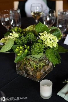 Pretty much what I have in mind but with taller vases.....green/ivory flowers with river rocks at the bottom of the vase