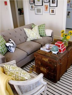 Really like the grey couch with pops of green and yellow, the frame wall, and the old wooden trunk as coffee table.