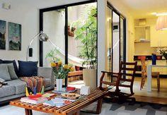A harmonia impera no living, integrado à cozinha, que recebe luz natural através do jardim interno. Ali, o empresário André Tassinari descansa na rede e curte o convívio com as plantas