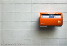 The floating mailbox  big orange mailbox hanging on a gray wall.  made with Fuji X20