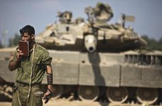 An Israeli soldier prays in front of a tank at a military staging area near the border with the Gaza Strip July 24, 2014.