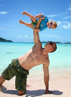 Man doing exercise using his child as his weight