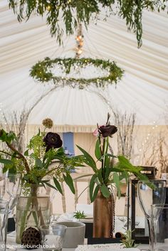 Hanging floral rings and an arch dividing the marquee adds to the drama within the venue. A Wilde Bunch marquee design Marquee Wedding, Canopy, Garland, Wedding Flowers, Arch, Drama, Table Decorations, Weddings, Rings