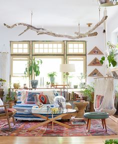 Eclectic living space with branch hanging from ceiling, lots of colors and indoor plants