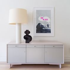 Subtle color: A vintage credenza turns modern thanks to paint—shades of pale pink and gray from Farrow & Ball. The posters and art throughout the house were finished with Framebridge frames.