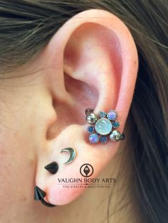 Here is a healed conch piercing we did for Margie a little over a year ago. She had us custom order her this lovely @anatometal captive gem cluster. She chose this gorgeous combination of light purple opals and teal opals surrounding a genuine moonstone. Great choice, Margie. It looks amazing on you! @vaughnbodyartsMonterey, CA
