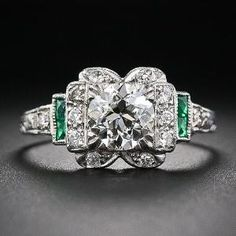 A strikingly beautiful, original Art Deco engagement ring distinctively designed and masterfully rendered in platinum - circa 1930. The ring centers on a dazzling 1.02 carat European-cut diamond that is embellished on all four sides with small diamond sparklers. The north and south sides evoke stylized bows and the east and west sides are accented with bright green scissor-cut calibre emerald by April*