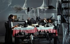 A kitchen with a large table is full of Halloween decorations.